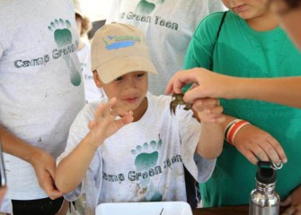 A staff volunteer explains the importance of crayfish to a healthy ecosystem