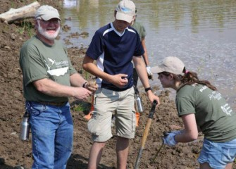 Joe McMullen, Principal Environmental Scientist, Terrestrial Environmental Specialists, finds a frog while planting.