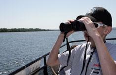 A student examines native wildlife on the shore of Onondaga Lake.