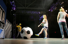 Katie Krafft, an eighth grader from Liverpool Middle School, kicks a massive soccer ball to demonstrate Newton's Second Law of Motion.