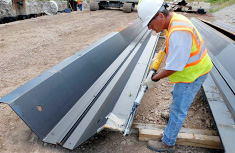 Contractors put a sealant into the groove of each interlocking joint to form a water-tight seal between panels. The steel panels are connected by sliding the interlocking joints together.