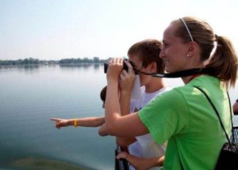 A Graduate Student from SUNY-ESF Shows Honeywell Summer Science Week Participant How to Use Binoculars to View Native Birds on Onondaga Lake.