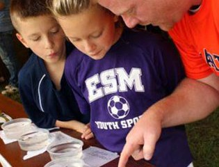 East Syracuse-Minoa Science Teacher John Herrington and His Two Children Examine Aquatic Bugs that Were Collected from Nine Mile Creek, Skaneateles Creek, and Carpenter's Brook.