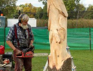Chainsaw Artist Mike Wilson Carves a Trout at Honeywell Sportsmen's Days.