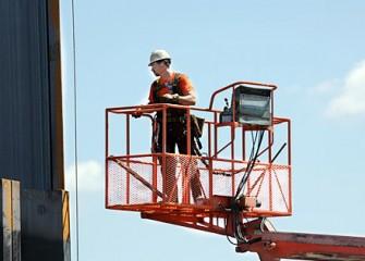 Worker Inspects Steel Panel