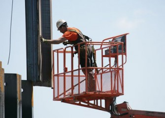 Worker Helps Guide Panel into Place