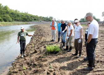 Volunteers prepare to plant native species. The plants will help re-establish wetlands and improve habitat and the ecosystem, creating a productive, healthy Onondaga Lake watershed.
