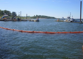 A silt curtain to help control water quality is deployed around a dredge area.