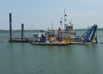 Largest dredge during final testing phase with support boat in the foreground.