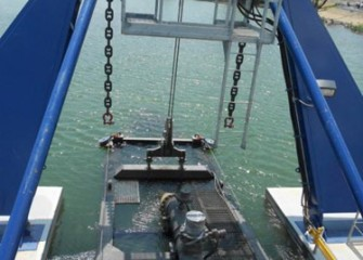 View from the dredge pilot house with cutter head lowered into the lake.