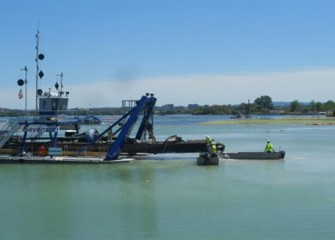 Workers perform routine maintenance on the dredge cutter head to keep it free from pieces of debris.