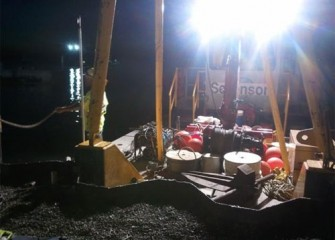 A crew prepares for night maintenance work on a support barge.