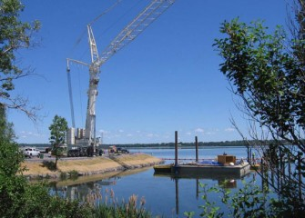 The crane is deployed near an area where debris will be removed before dredging