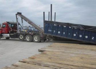 Containers are covered and transported to the debris management area at the consolidation area