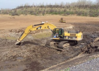 Worker uses an excavator to move clean soil to build the new wetlands