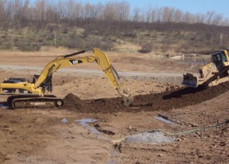 Workers place clean soil in the new wetlands