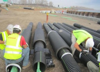 Workers prepare tension rods to support construction staging area.