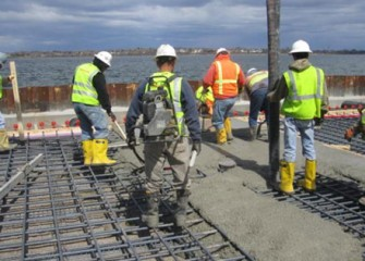 Workers pour concrete for concrete pad.