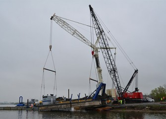 Two cranes safely place a dredge into the lake.