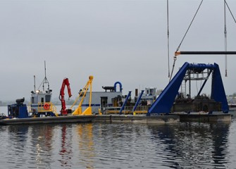 A support barge pushes the dredge into place to continue assembly.