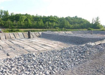 Concrete slabs are placed above the gravel to protect the liner.