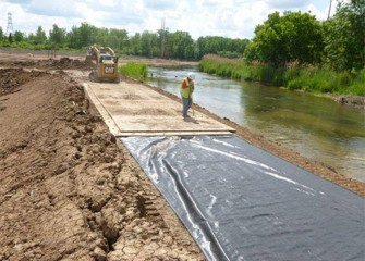 Workers prepare the banks for heavy equipment to access the creek.