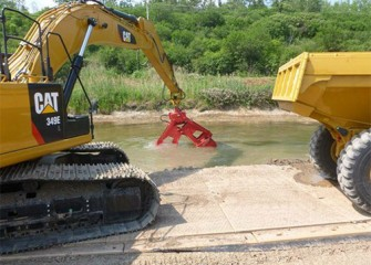 Excavators pick up the material and place it into waiting dump trucks.