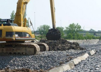 Excavators place dried material into trucks that transport the material to a separate landfill for final storage.