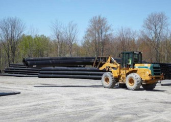 Sections of double-walled pipe assembled by Vari-Tech LLC in Liverpool, NY are stacked for delivery.
