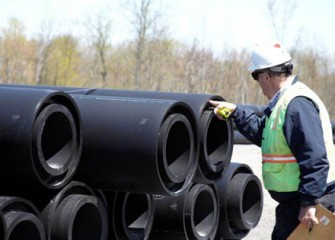 A worker examines sections of the double-walled pipe before delivery.
