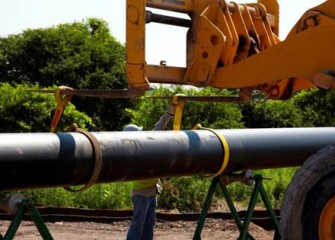 Sections of pipe are lowered into place as construction of the pipeline begins.