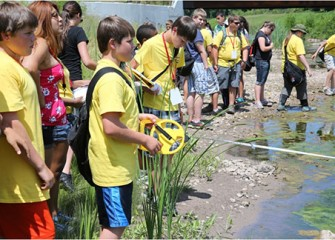 Summer Science Week students conduct stream profiles at Onondaga Creek, measuring the width of the stream and the depth of the water