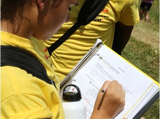 A student records findings and observations in her Honeywell Summer Science Week at the MOST notebook.