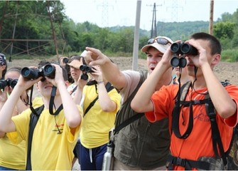 Experts from Montezuma Audubon Center and Onondaga Audubon Society lead students on a birding walk to track native species at the Geddes Brook wetlands
