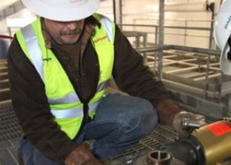 Worker installing equipment that will blend chemicals to treat water