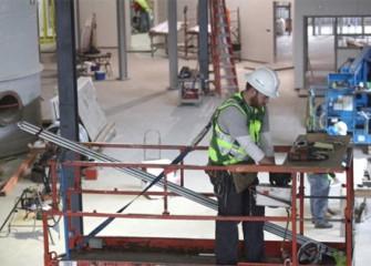 Worker installing lighting conduit