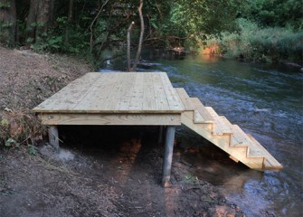 A dock is installed upstream along a trail.