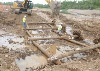 "Logs are guided into place to form a ""crib wall"" that will help stabilize the creek channel and provide habitat."