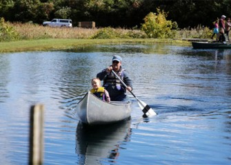 Neil Anderson, of Auburn, New York, paddles as Connor Ryan, also of Auburn, enjoys a canoe ride at the 2012 Honeywell Sportsmen's Days.