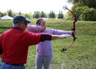 Olivia Haines, of Marcellus, N.Y., learns to shoot with help from a local sportsman.