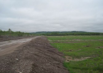 Preparation to build the consolidation area begins with roads and containment berms.