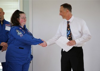 Math Teacher Mary Newman of Hughes Pre-K – 8 School (Syracuse) is welcomed to Honeywell Educators @ Space Academy.