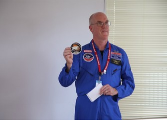 Honeywell Educators @ Space Academy 2012 alumnus Dan Howard, Technology Teacher at West Genesee Middle School, displays his Apollo 13 patch while discussing lessons learned at Space Camp.