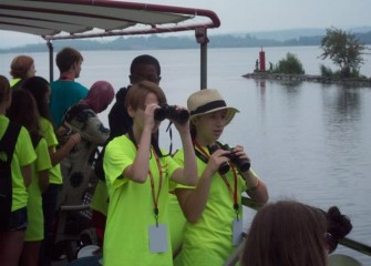 As the Emita II leaves Seneca River and enters Onondaga Lake, students use binoculars to spot birds.