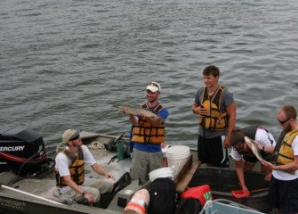 SUNY-ESF research assistants show students samples of fish living in Onondaga Lake.