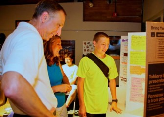 Honeywell Syracuse Program Director John McAuliffe (left) joins parents in viewing student posters before the recognition event.