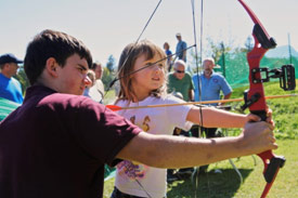 Eagle Scout Andreu Nutter, of Cicero, N.Y., teaches Darby Ryan, of Sennett, N.Y., how to shoot an arrow at the <em>2013 Honeywell Sportsmen's Days at Carpenter's Brook</em>.
