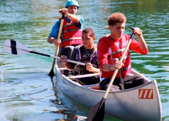 Marcus Landers (front), Donavan Lynn (center), and Quentin Lynn of Syracuse paddle across the pond.