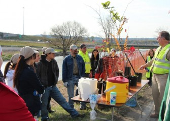 Ray D'Hollander, Parsons environmental engineer and Corps volunteer, shows participants native trees they will help plant.