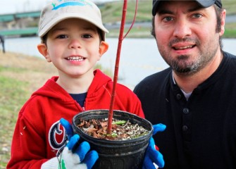 As new plants mature, this young Corps volunteer will be able to look back and remember when he helped plant this tree important to the Onondaga Lake watershed.